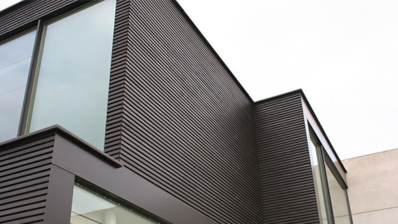 A close up of exterior wooden siding finished in a dark exterior wood oil.