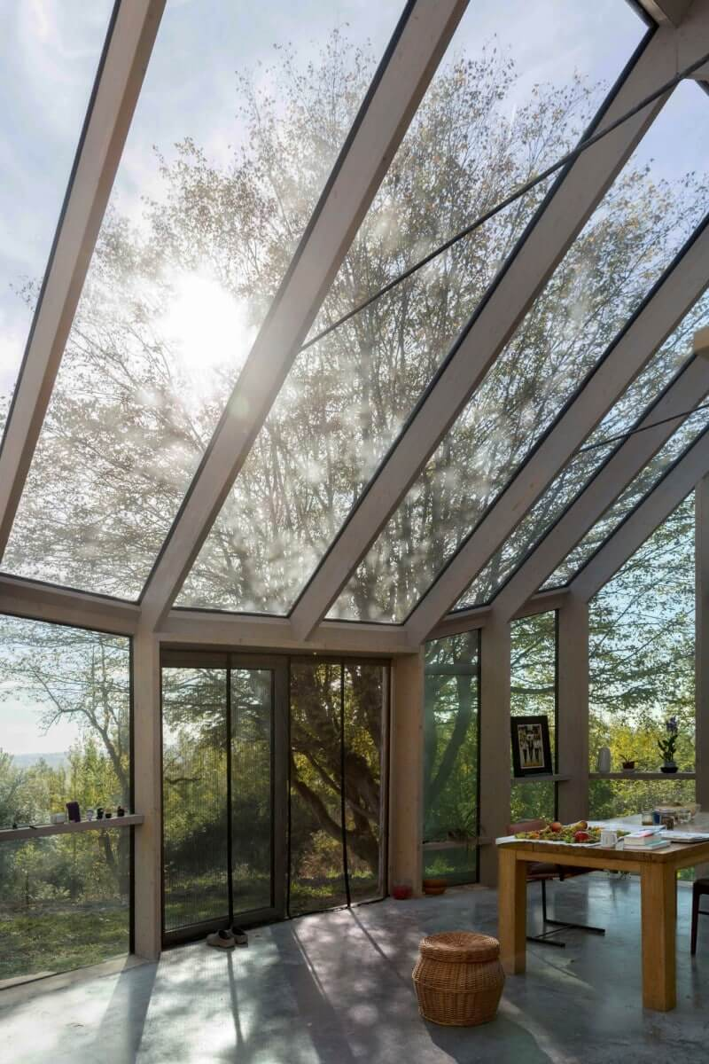 Glass sun room with wood beams inside.