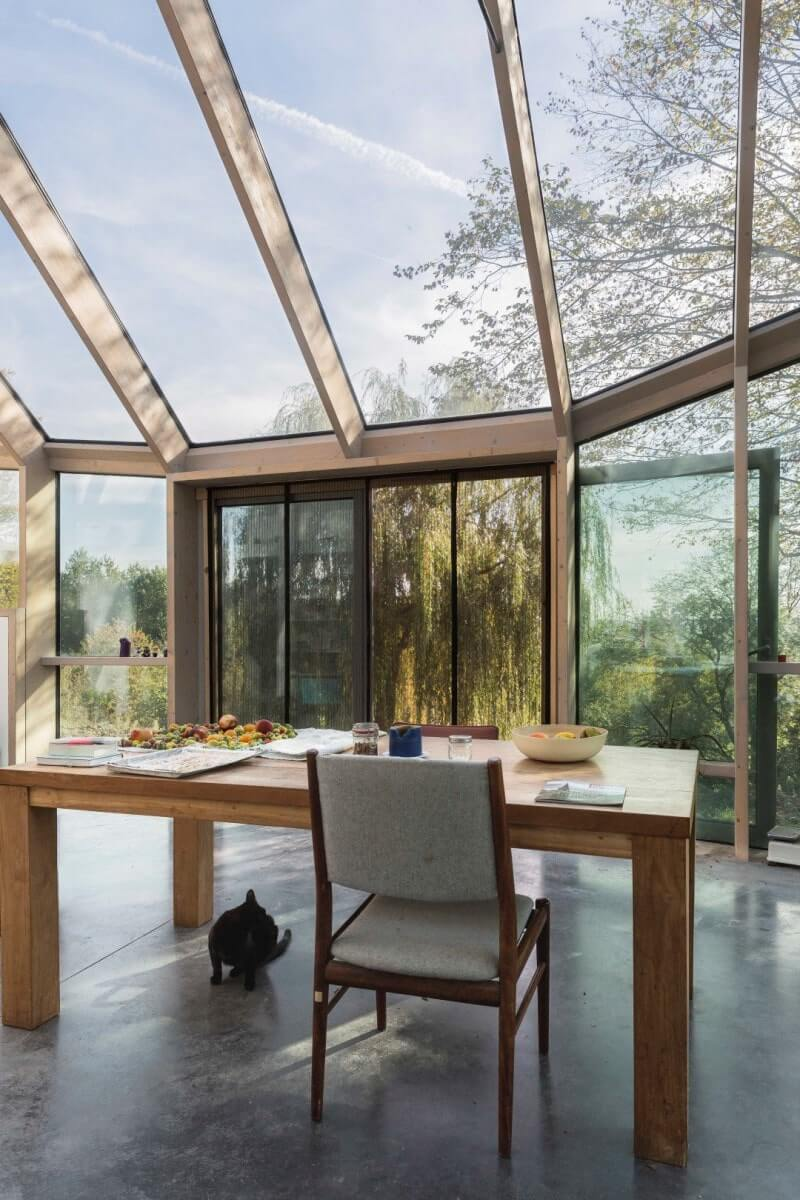 Table in glass sun room with wood beams.