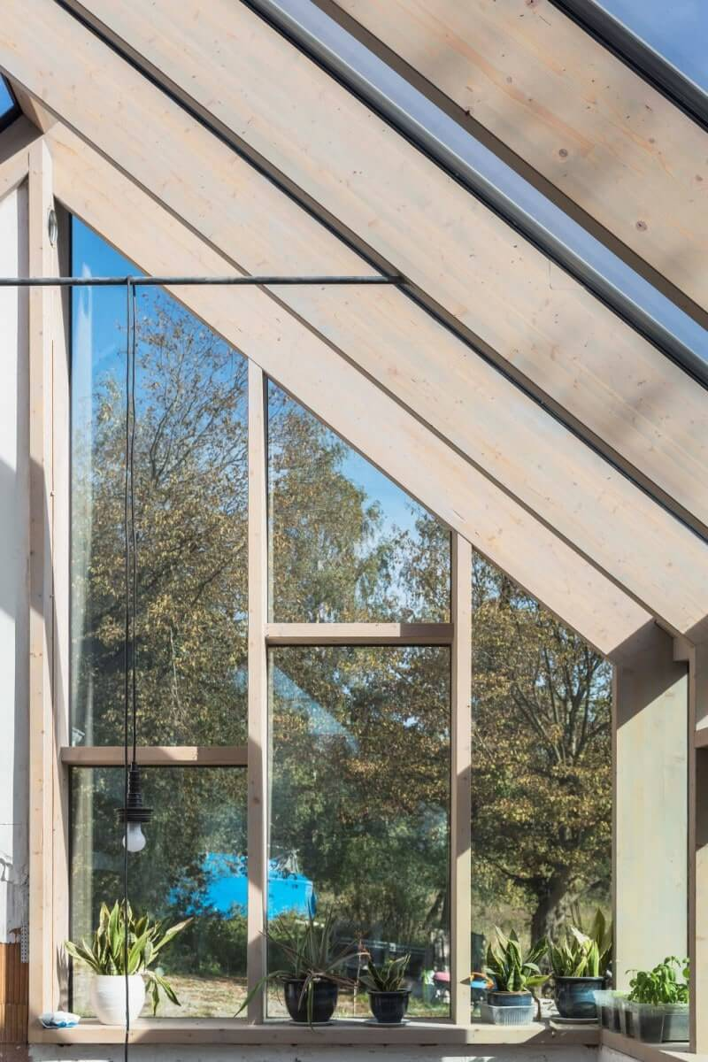 Wood beams holding up glass panels in a sun room.