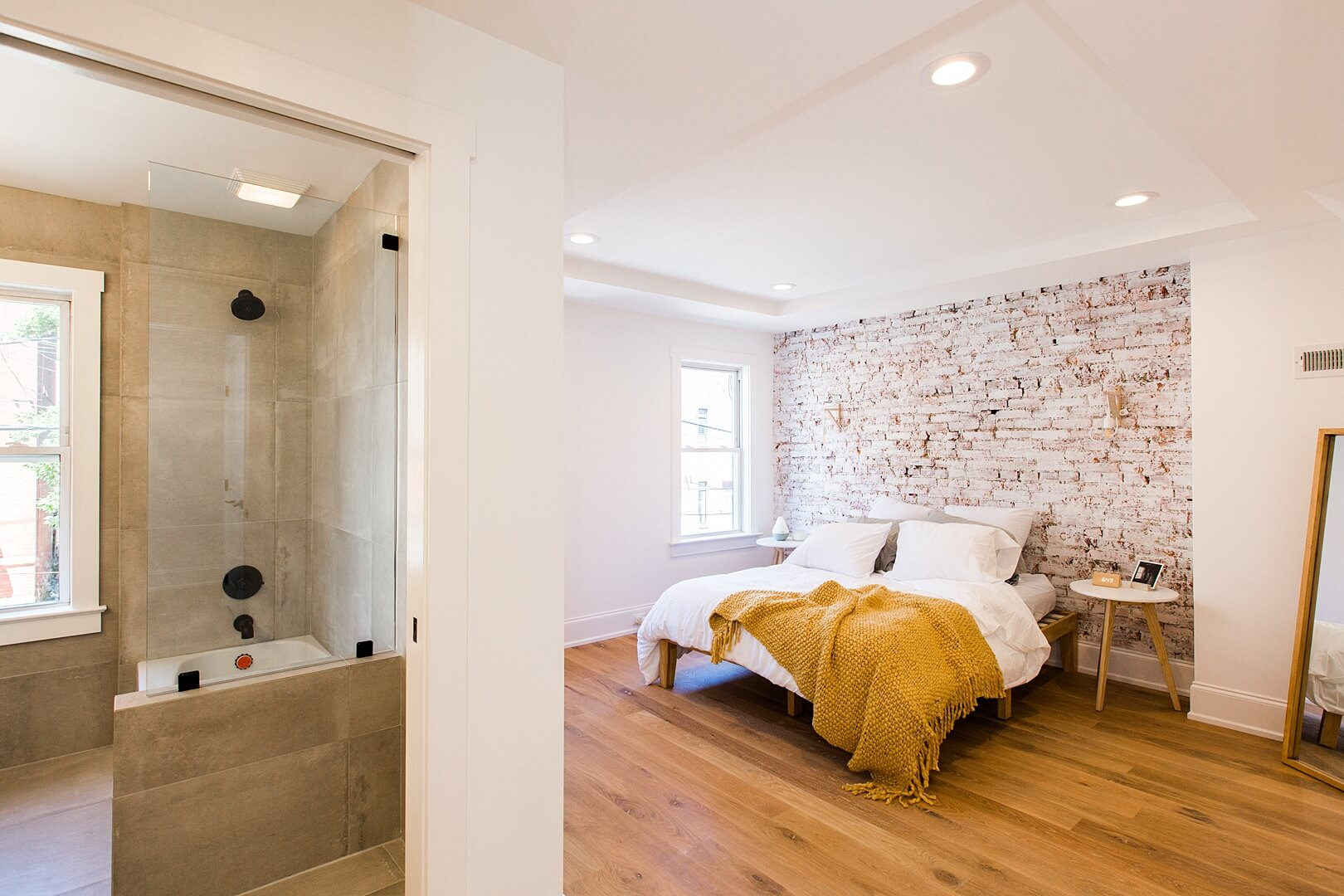 Master bedroom with hardwood flooring and a brick accent wall.