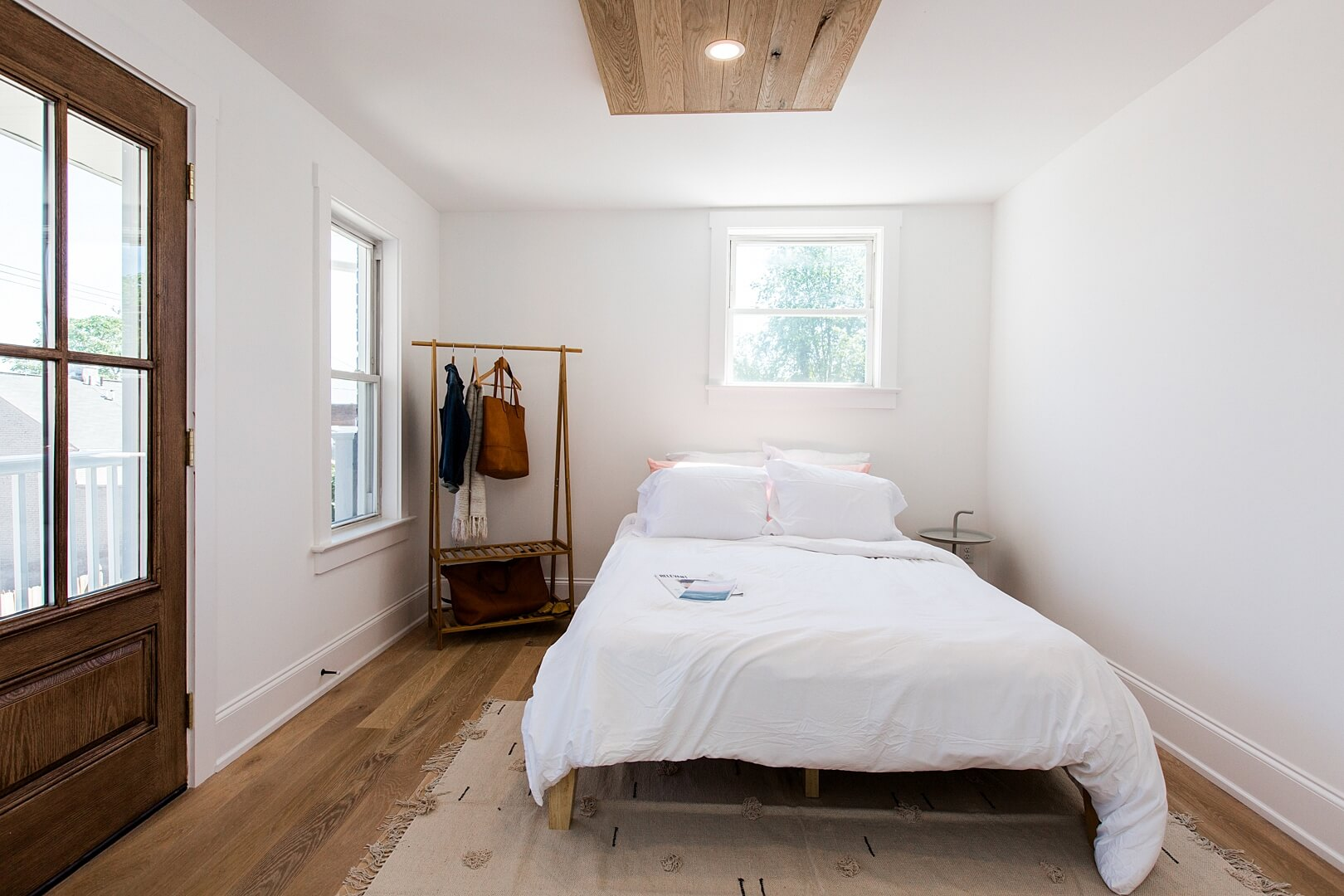 Bedroom with hardwood flooring and a white oak ceiling accent.