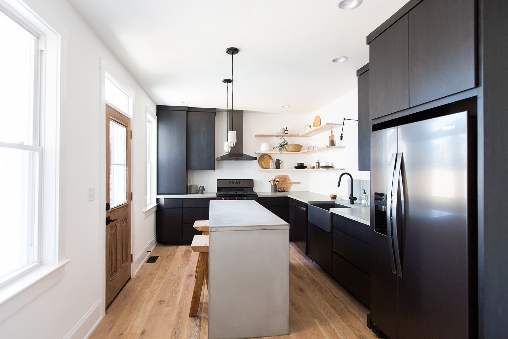 Modern kitchen with white oak floors and dark cabinets.