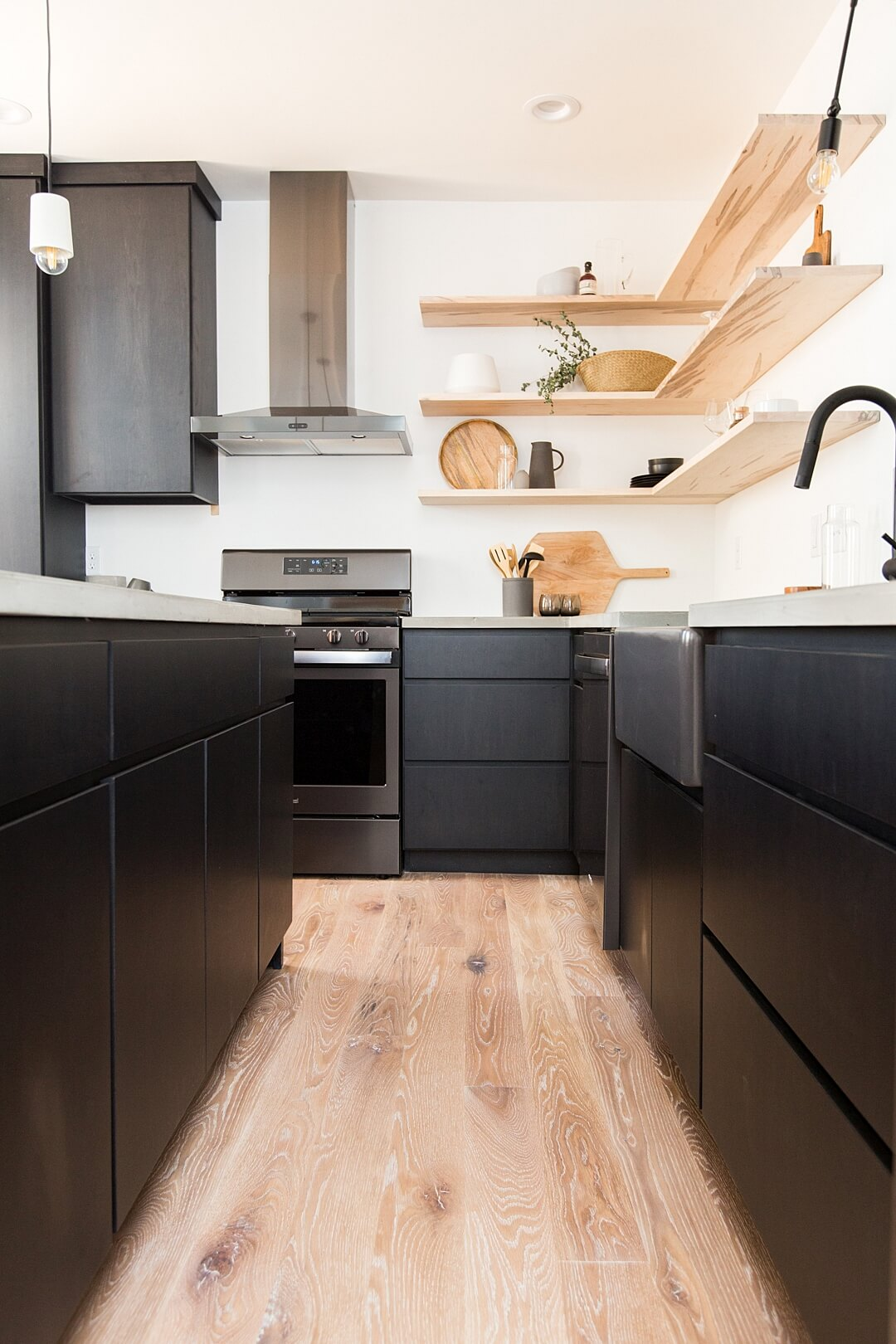White oak flooring in a modern kitchen that had black cabinets and white oak floating shelves.