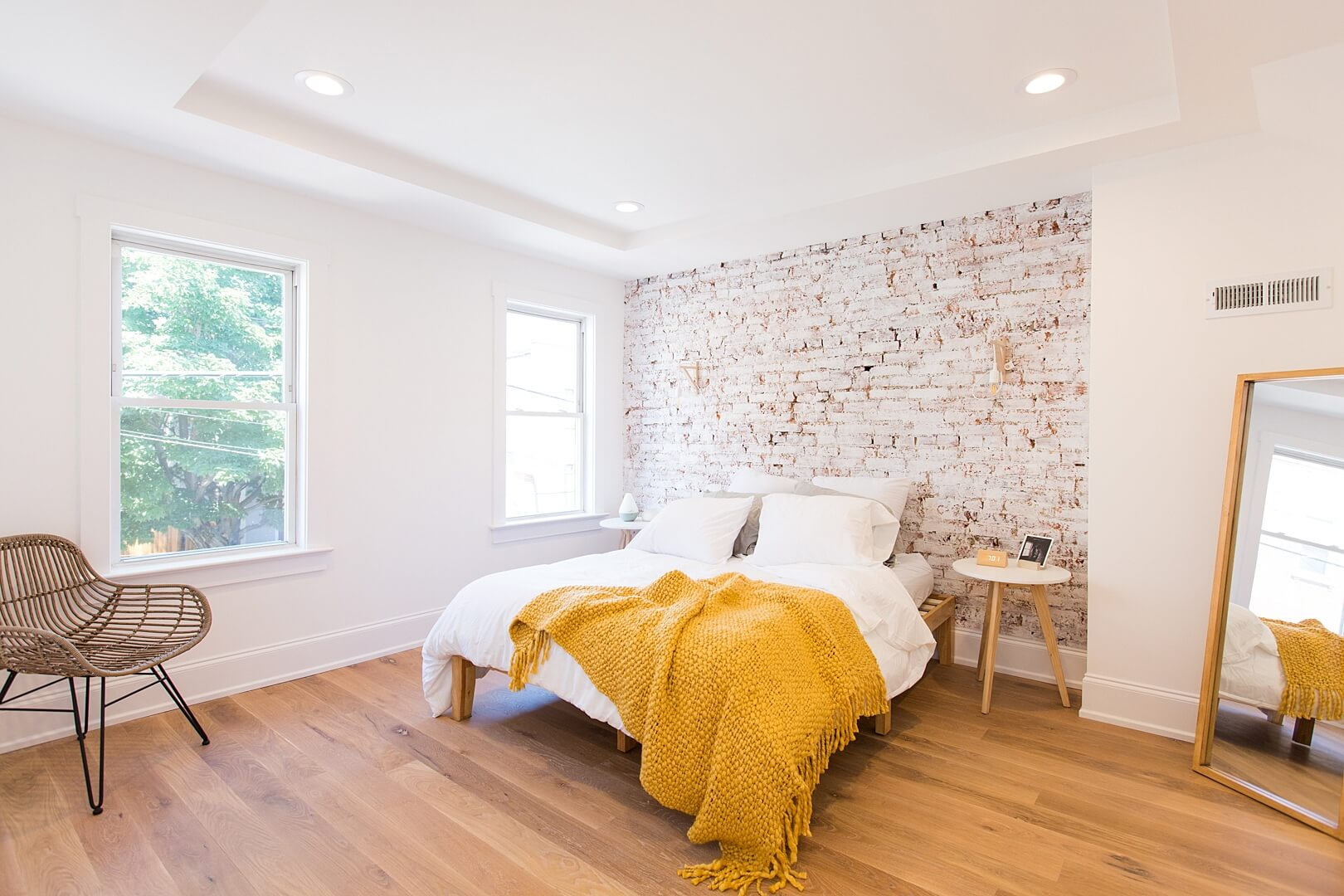 Bedroom with hardwood flooring, bed and brick accent wall.