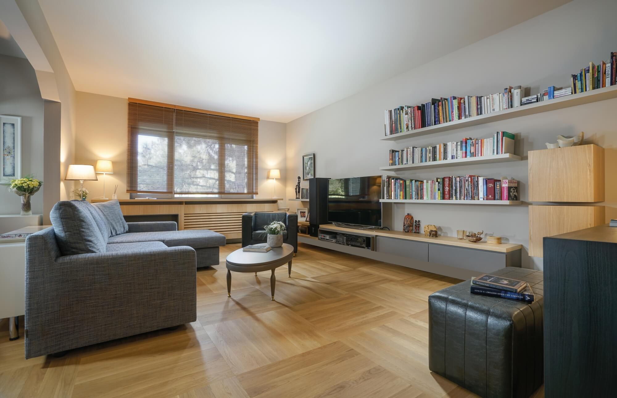 Parquet wood flooring in a living room with floating shelves.