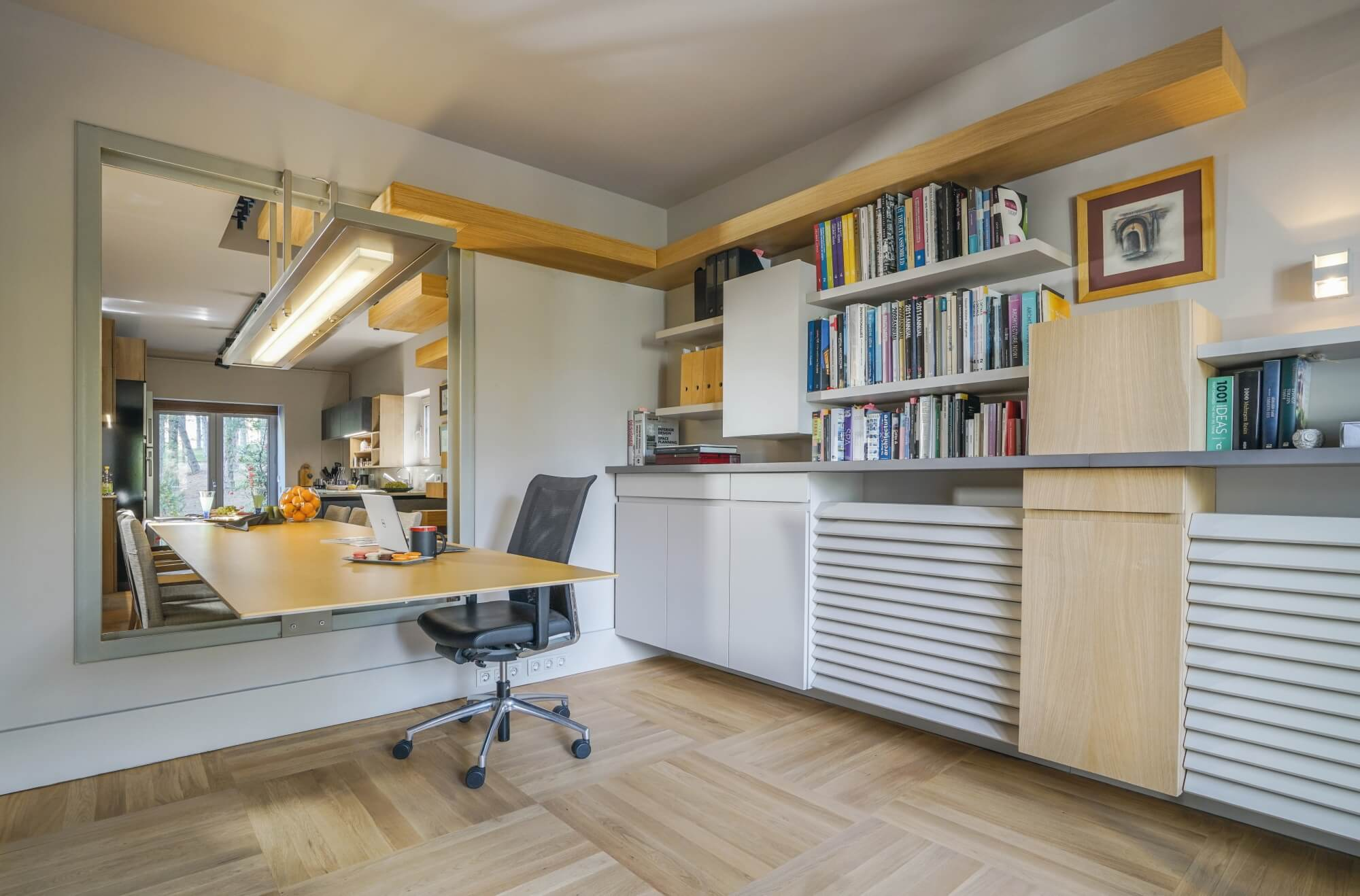 Home office with desk passing through a window for use in and out of the office.