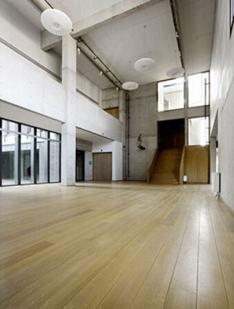 A large room in a school with hardwood flooring