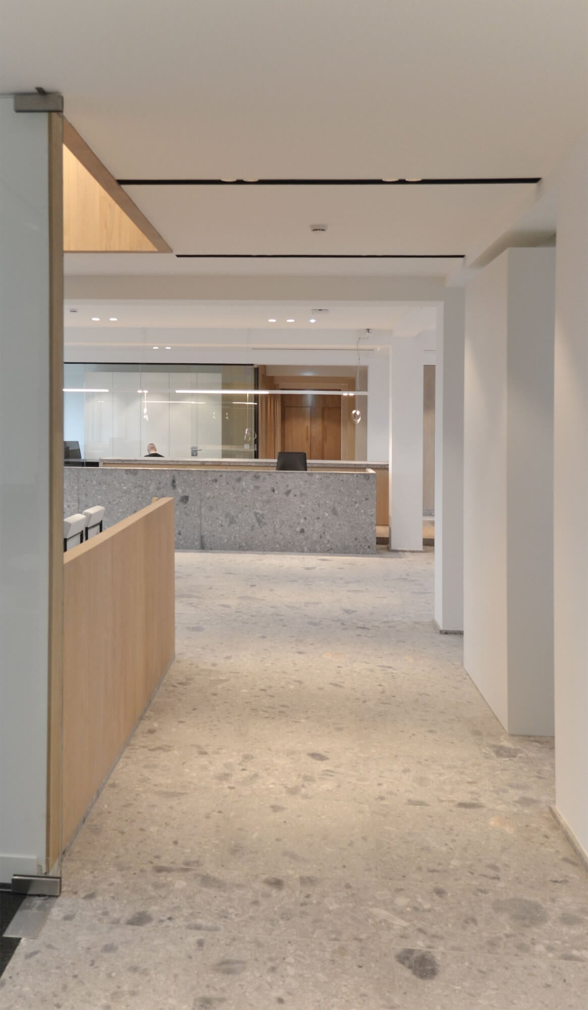 Office building with concrete flooring and wood cubicles.