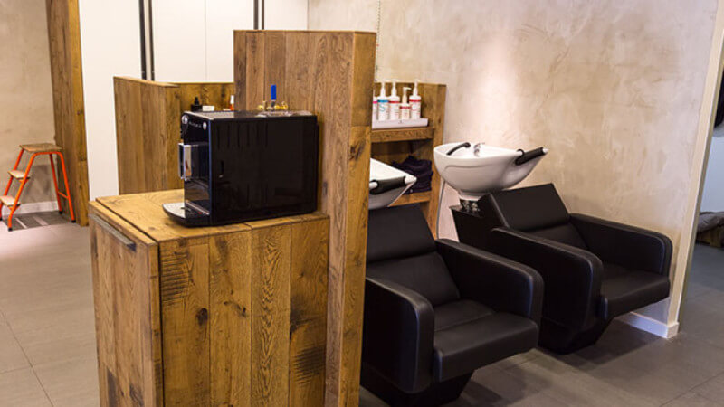Two chairs in a barbershop with a wood cabinet standing beside it.