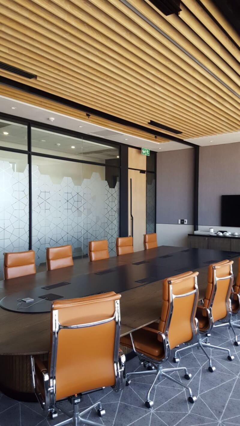 Wooden cladding on ceiling of conference room.