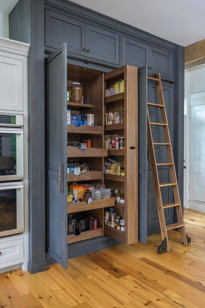 Custom stained rift and quartered white oak pantry cabinet in a kitchen.