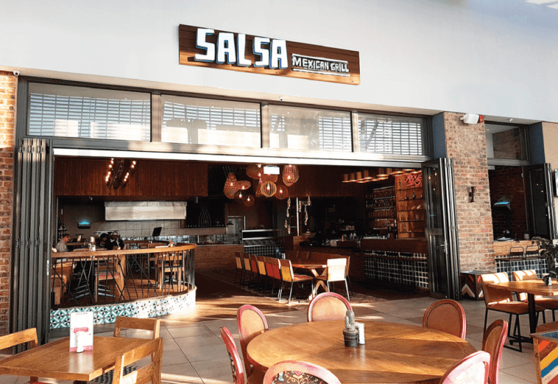 The storefront of Salsa, a mexican restaurant with matte finish wood details throughout.