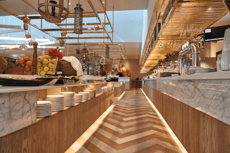 A matte finish herringbone floor inside a fine buffet style restaurant with matte finish cabinetry.