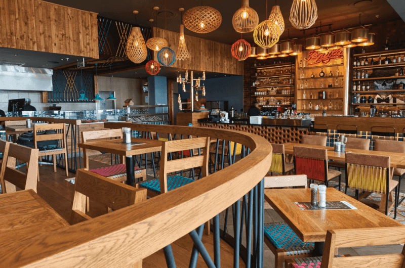 The interior of a mexican food restaurant style with natural colored wood throughout.