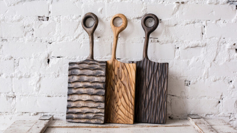 Wooden serving boards with hand carved textures on them.