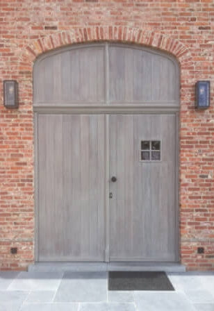 A large wooden door with rustic white wood finish on it.