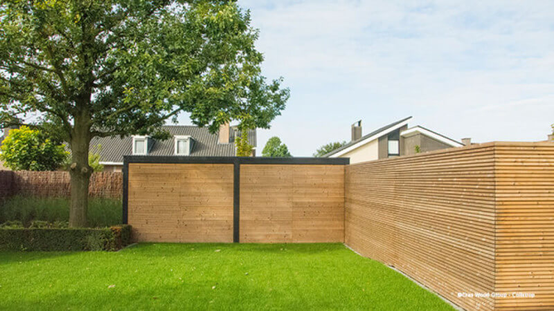 A a green yard with a fence finished using Rubio Monocoat exterior oil finish.