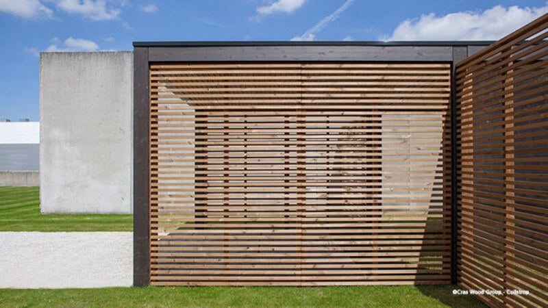 A carport with wood boards running lengthwise to create a barrier from the elements.