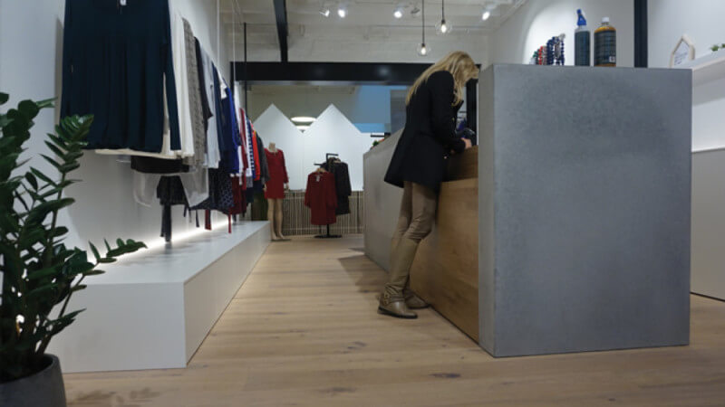 Front desk at a clothing store with wooden floors finished with Rubio Monocoat.