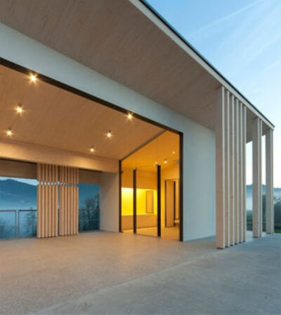 A cemetery building with vertical wooden columns that provide support and create spaces.