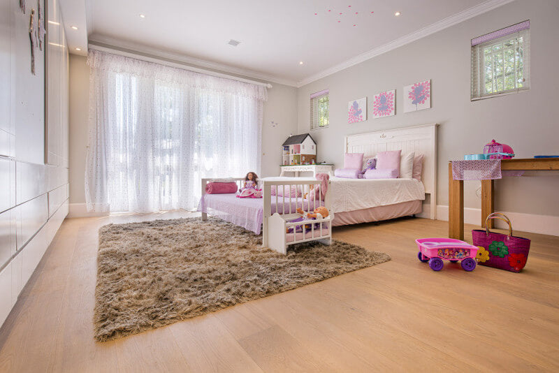 Young girls room with wide plank wood flooring in it.