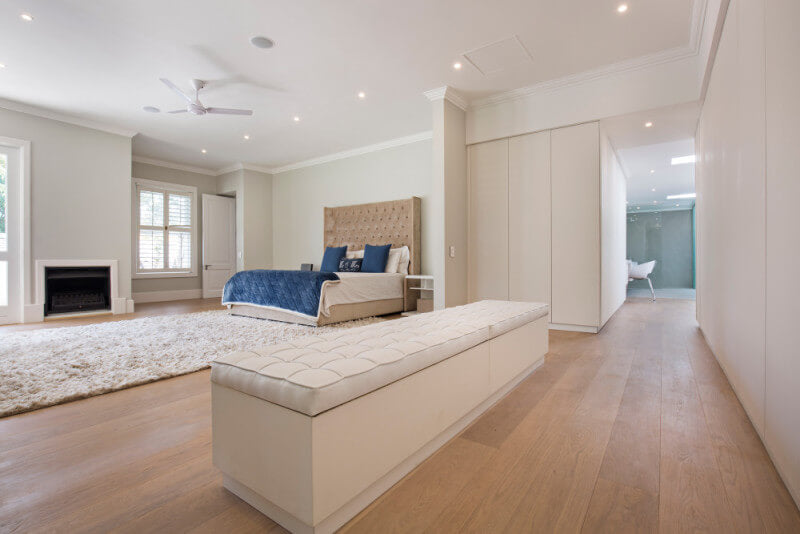 Natural colored wide plank wood flooring in master bedroom.