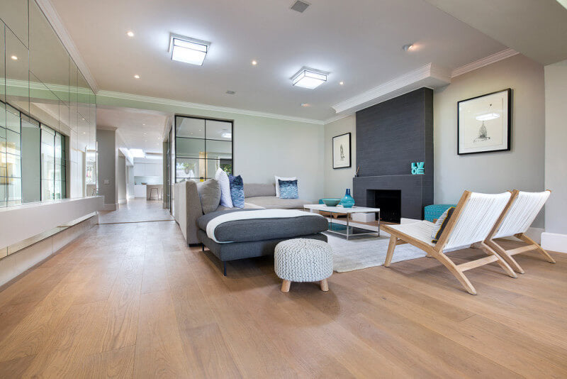 Luxury wide plank floors in a living room finished with natural floor finish.