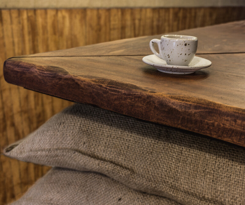 Close up of wooden counter tops and a cappuccino cup sitting on the counter.