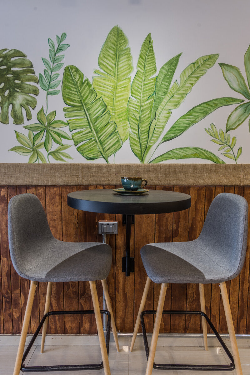 A commercial, 2 seat coffee table with chairs against wooden paneling on the bottom half of the wall and artwork on the top half of the wall.