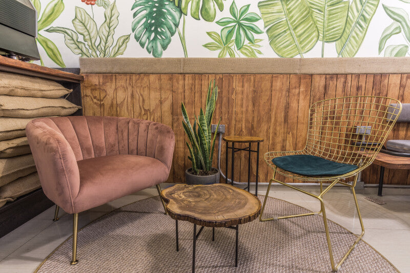 Different chairs and decor make up a cozy seating area inside a trendy coffee shop.