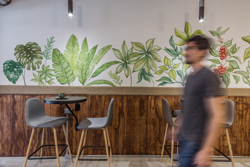 An out of focus man walking in the foreground with a trendy styled coffee shop interior in the background.
