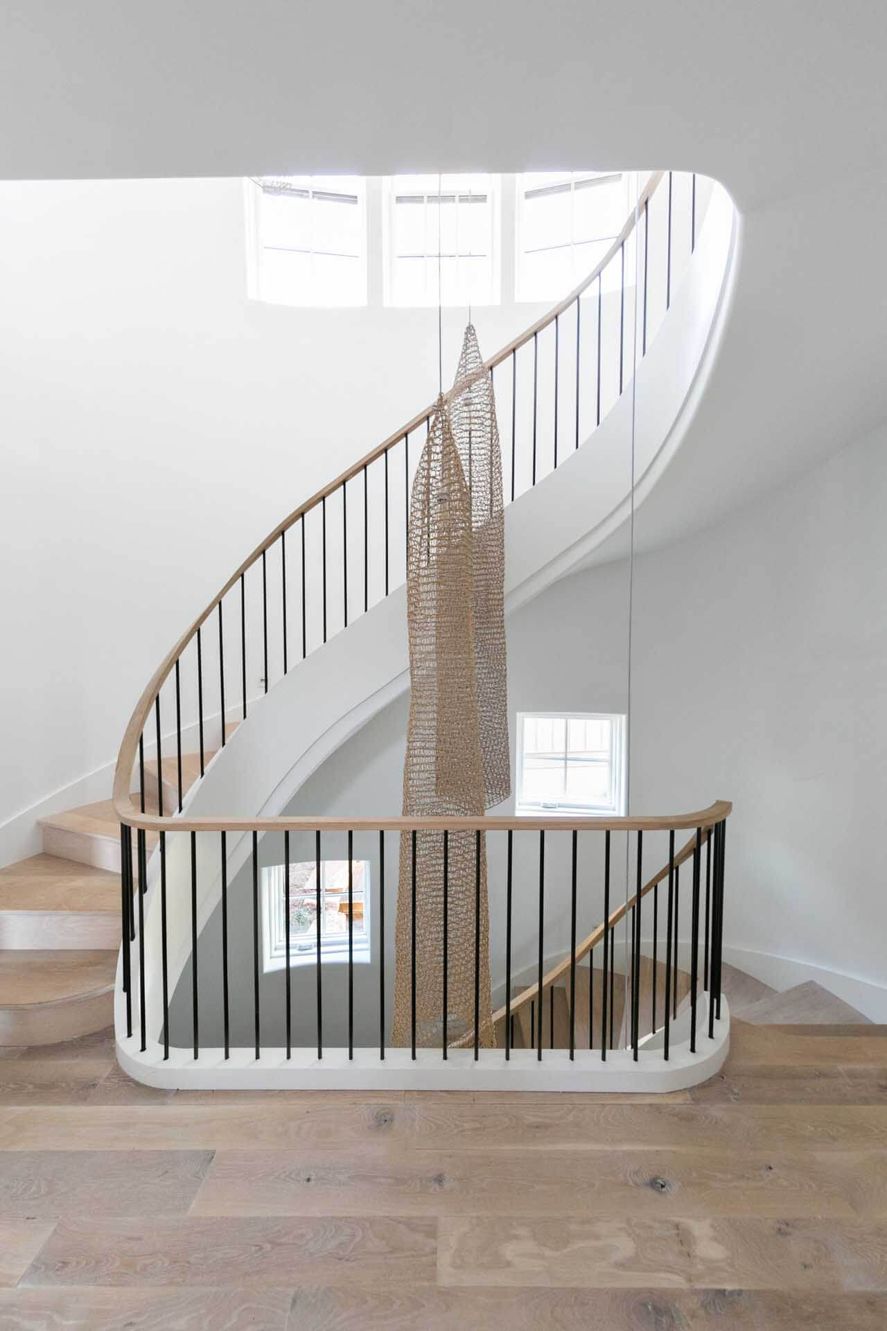 Winding staircase with hardwood treads and decor hanging down beside the stairs.