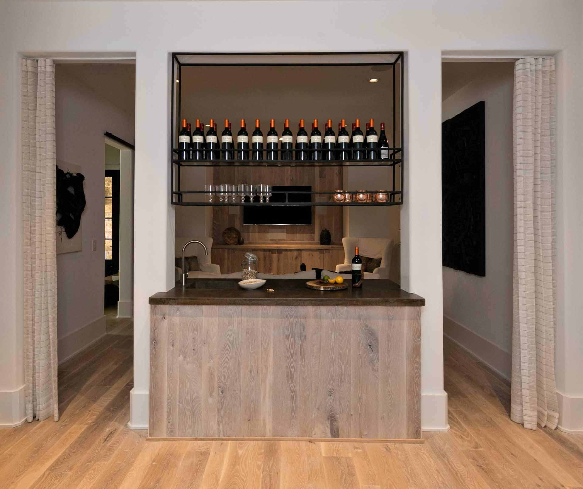 A white oak wet bar in a home with hardwood flooring.