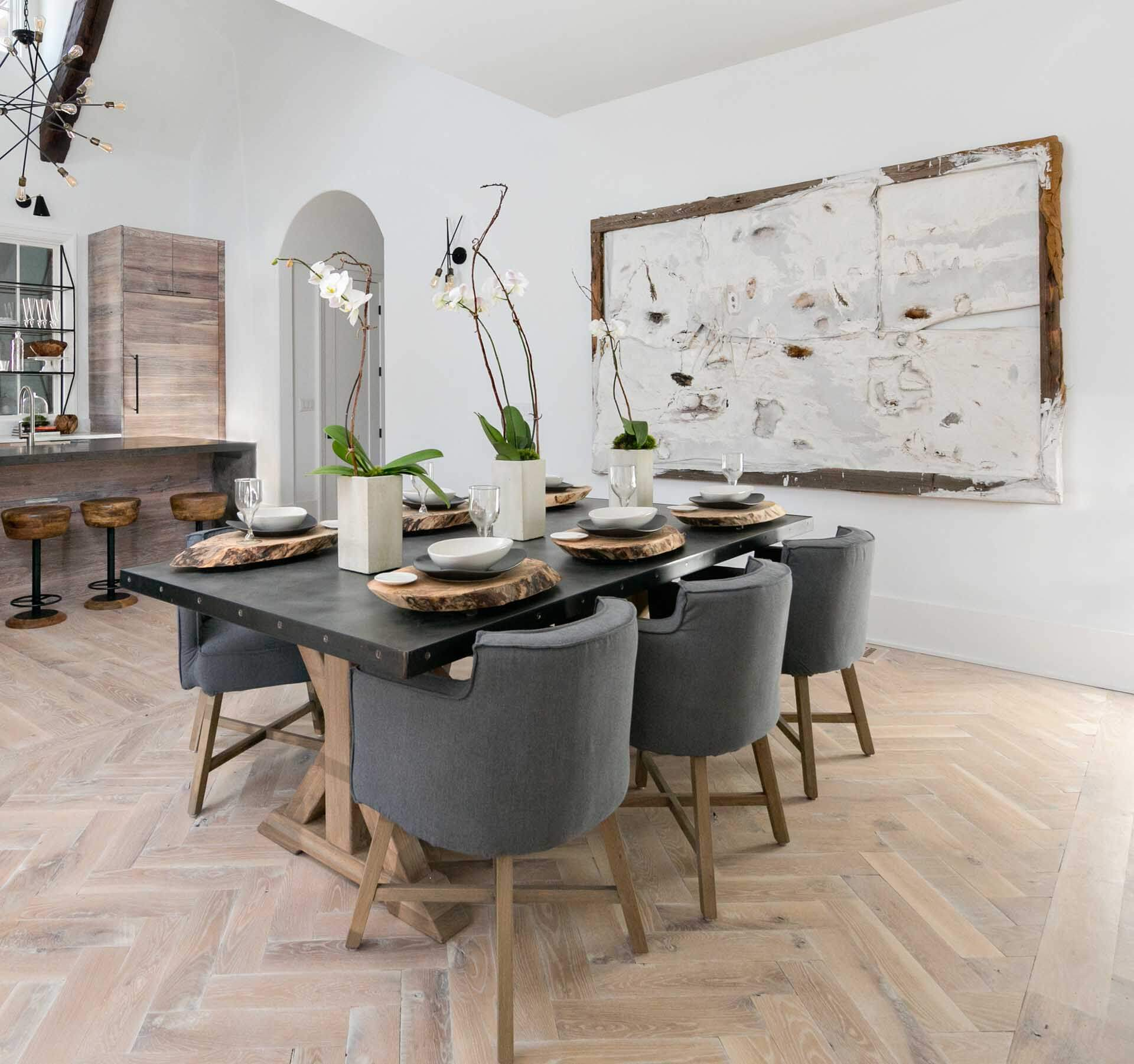 A dining area with herringbone hardwood flooring finished with a light matte wood finish.