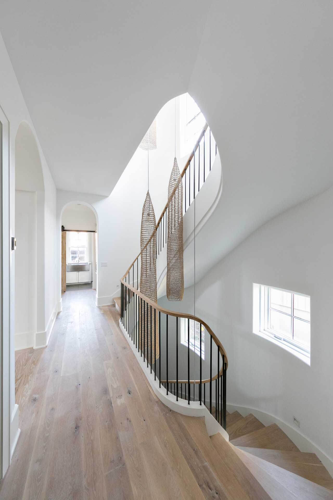 A wood staircase leads to a hallway with hardwood flooring.