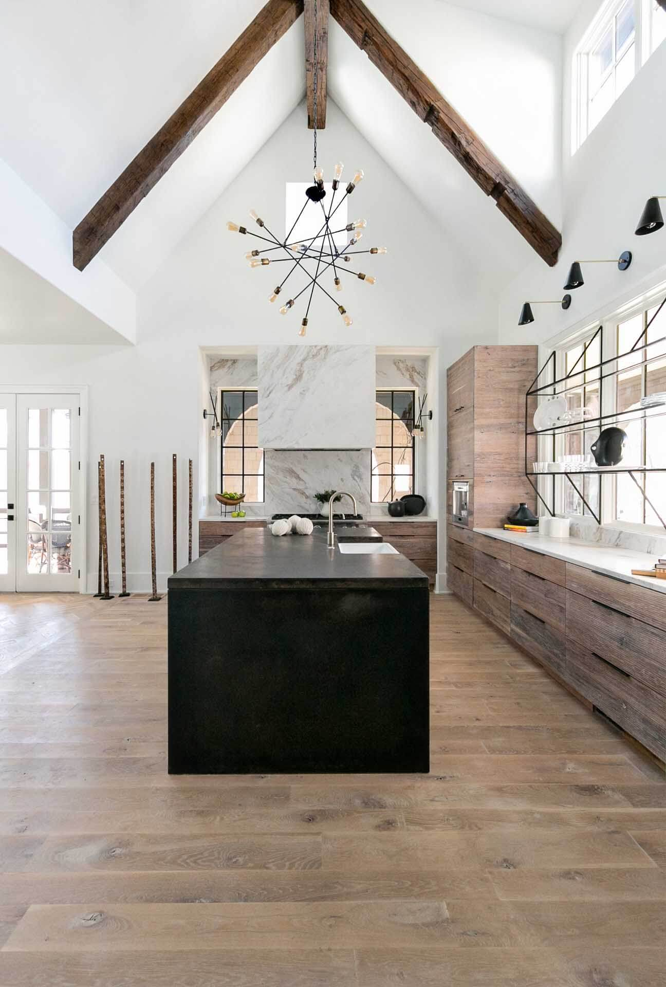 Light colored hardwood flooring and decor in a kitchen with tall ceilings, wood cabinets and a kitchen island.