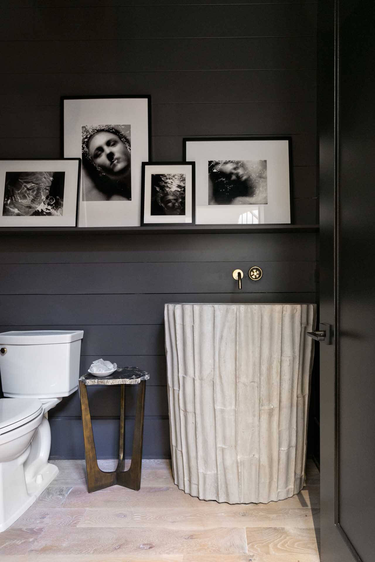 A powder room with dark accent walls and light decor.