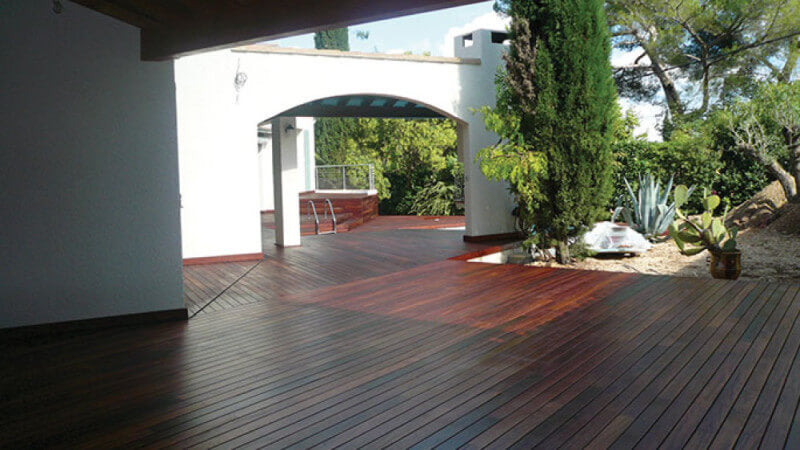 A large Ipe wood deck finished with a hardwax oil wood finish behind a house with trees and plants alongside it.