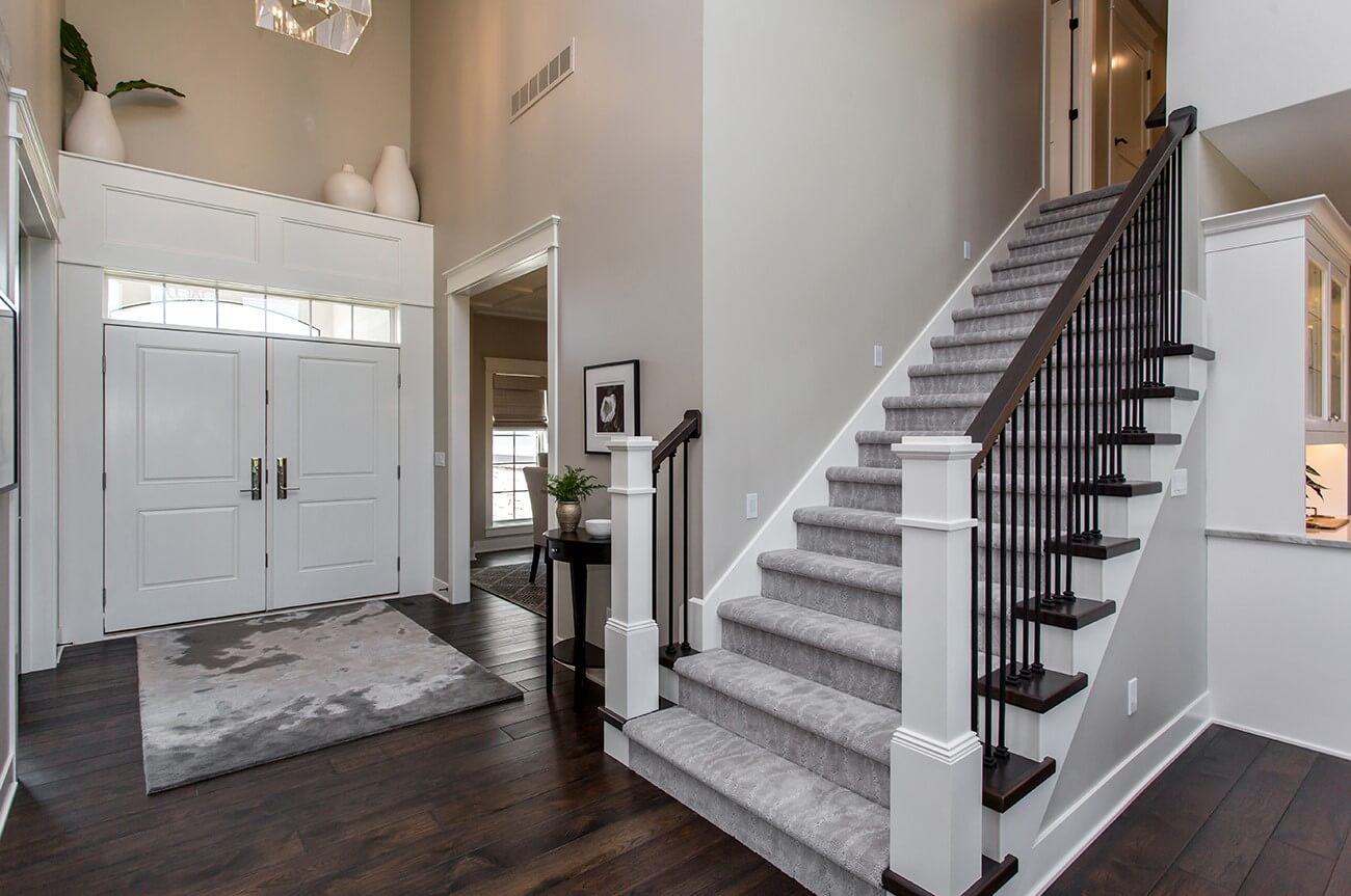 Dark wood flooring in an entry with a stairway leading upstairs.