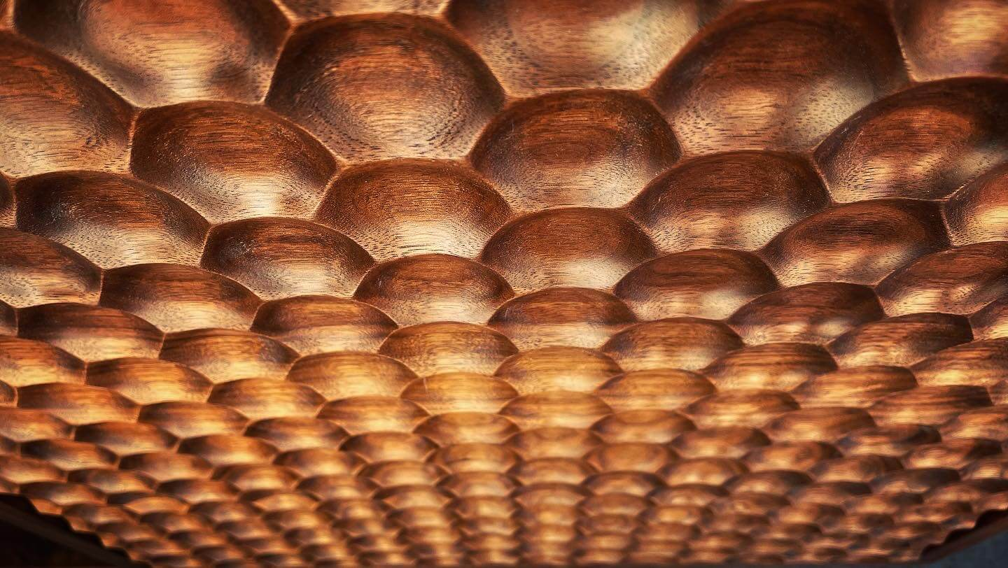Repeating honeycomb pattern milled into walnut wood.