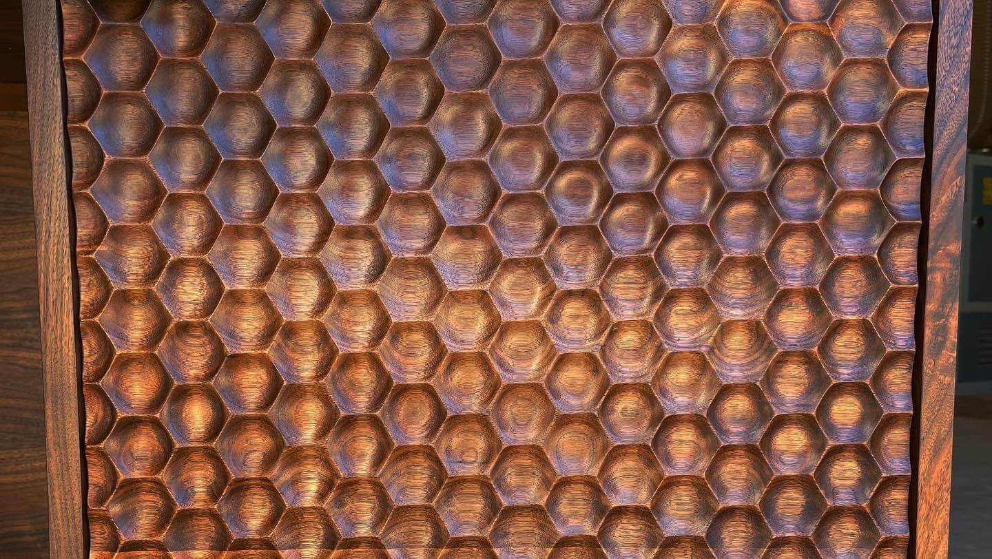Front view of repeating honeycomb pattern machined with a CNC into walnut wood.
