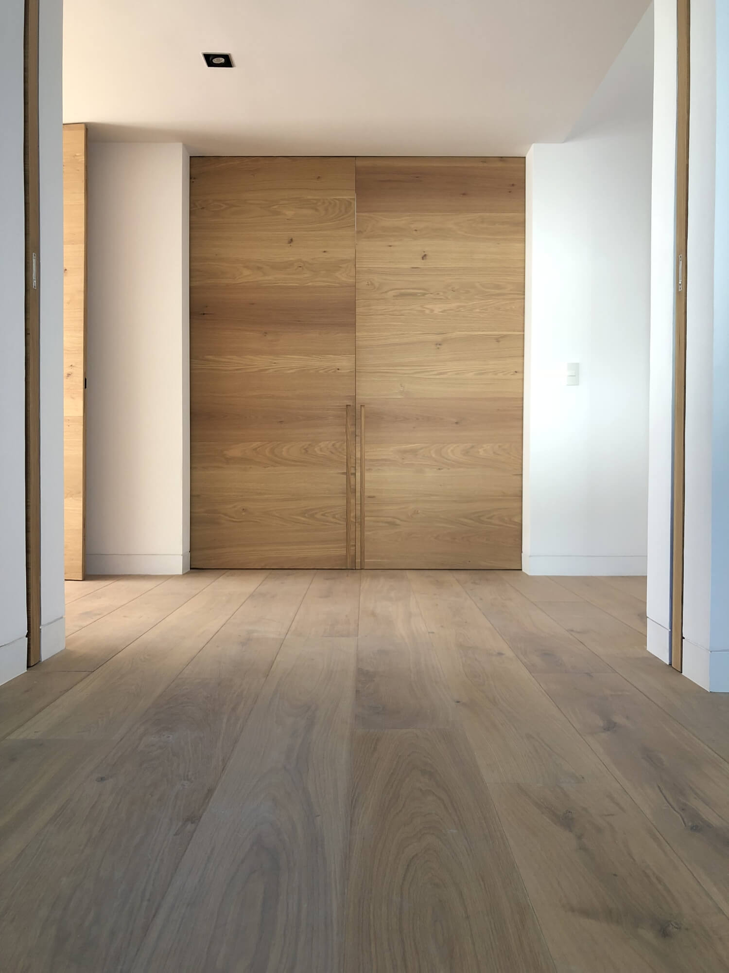 Wide plank oak flooring with white walls and natural color oak barn doors.