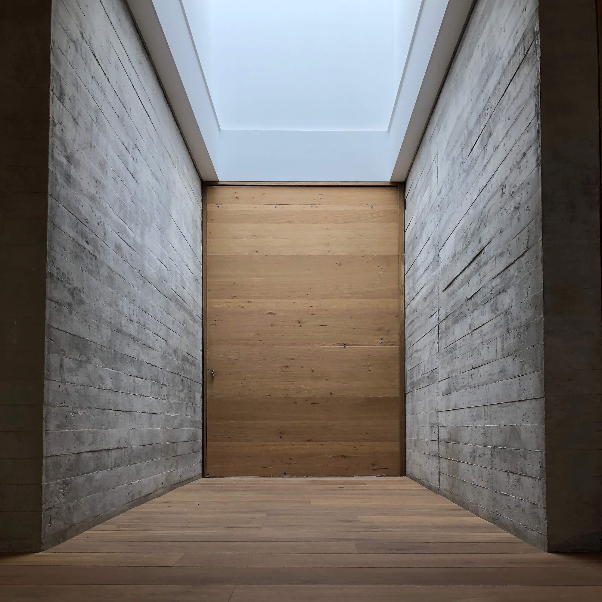 A concrete hallway with white oak flooring and door at the end.