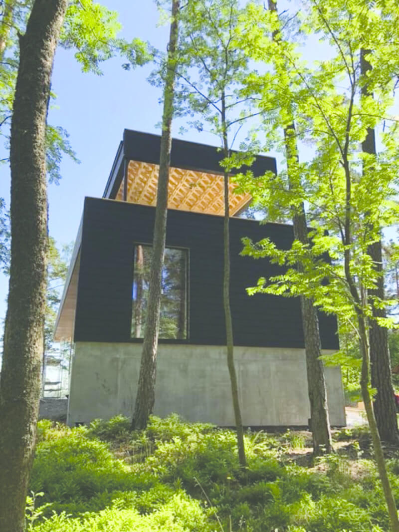 A modern home surrounded by trees.