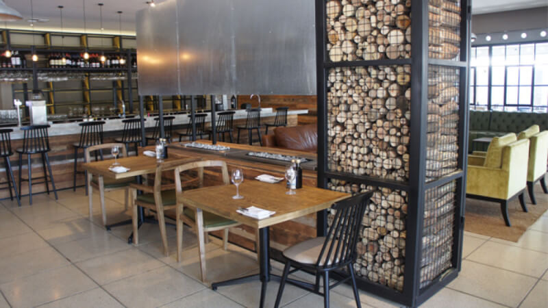 Rustic restaurant decor with wood logs inside a steel cage.