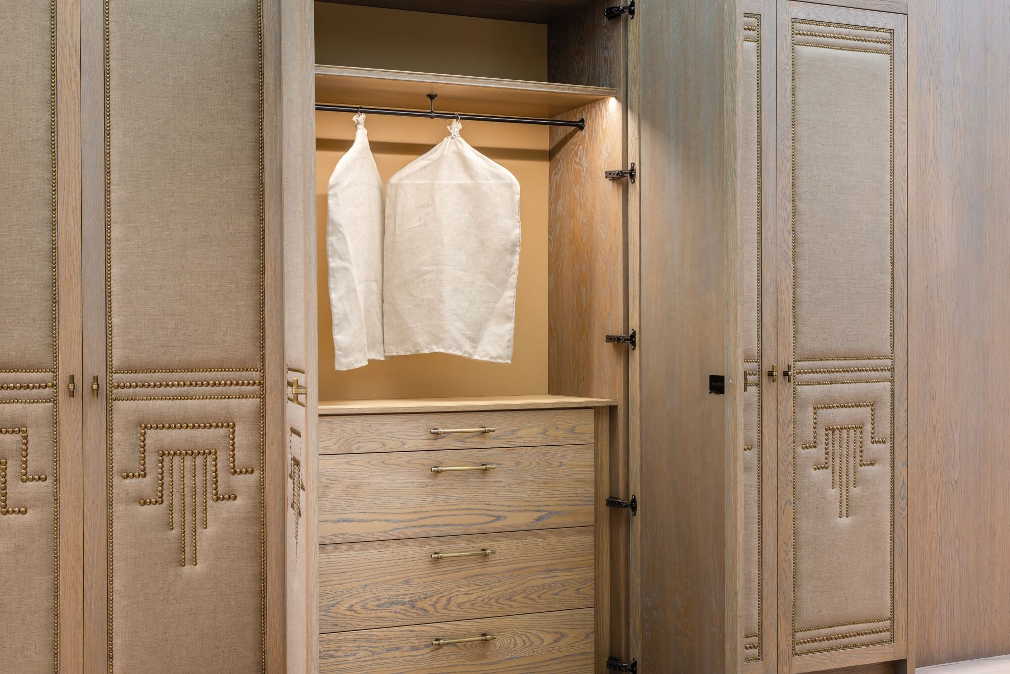 Luxurious bedroom with wood paneling and built in closets on the walls.