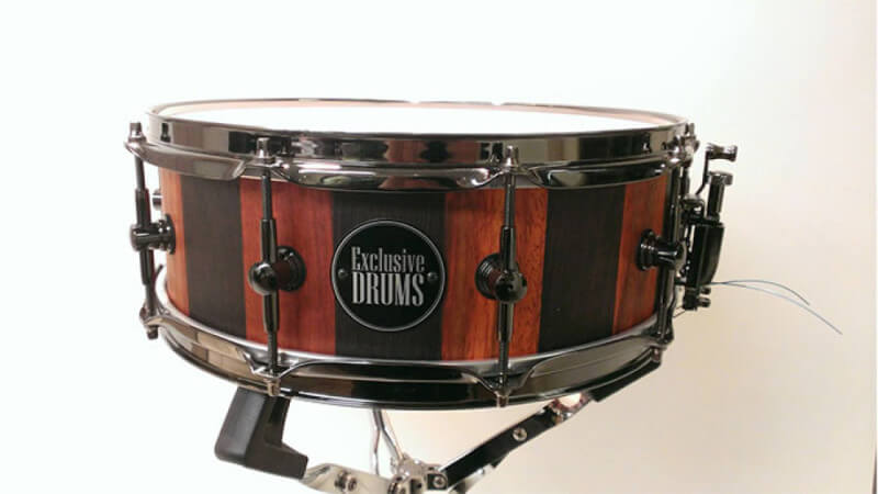 A custom stave wood drum shell made out of padouk and wenge with a matte wood finish.