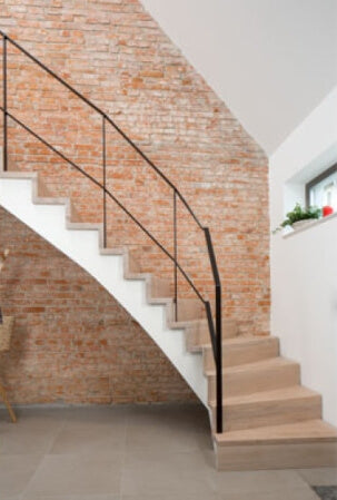 A curving stairway made out of oak wood and finished with a plant-based hardwax oil wood finish.