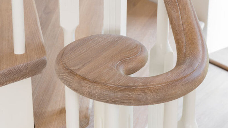 A curved handrail for stairs that is finished with a natural, plant-based wood finish.